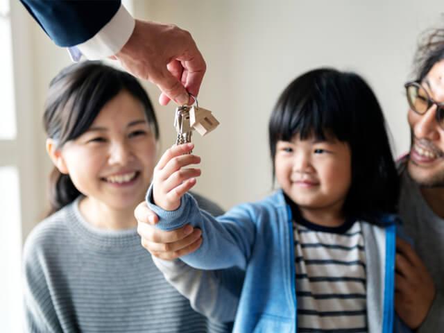 子どもに鍵を出している不動産スタッフ
